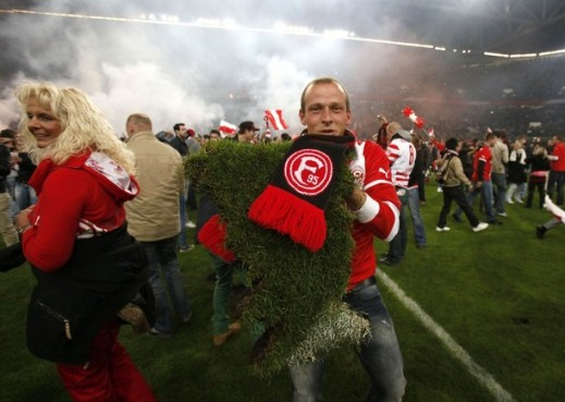 A Fortuna Duesseldorf fan shows a part of the pitch which he picked up after his team won its Bundesliga relegation soccer match against Hertha Berlin in Duesseldorf