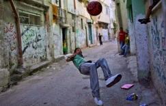 Un giovane palestinese salta per calciare il pallone, in un vicolo del campo profughi di Al-Amari a Ramallah