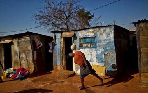 Una donna sudafricana mentre gioca con le altre donne, accanto alle loro case in una borgo di Soweto, alla periferia di Johannesburg, Sud Africa
