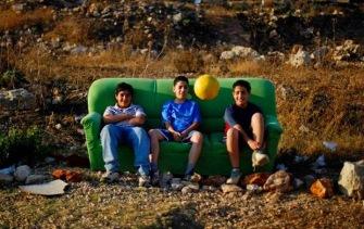 Giovani palestinesi seduti su un divano mentre guardano i loro amici giocare in un campo nella città di Ramallah
