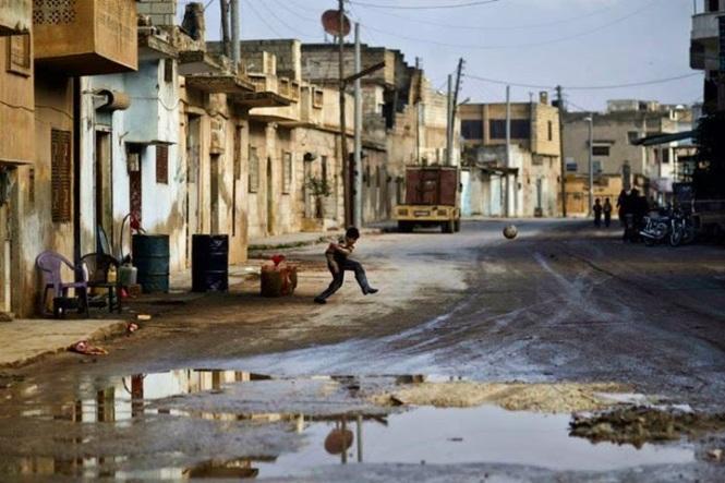 Un ragazzo siriano calcia il pallone a Maaret Misreen, nei pressi di Idlib, Siria