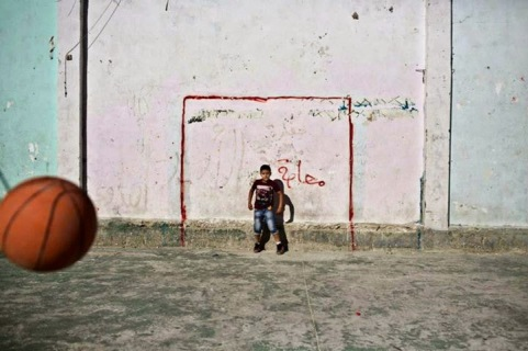 Ragazzi palestinesi usano un pallone da basket per giocare a calcio nel campo profughi della West Bank di Jalazoun