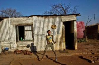 Un ragazzo sudafricano salta per prendere la palla in uno borgo di Soweto, alla periferia di Johannesburg, Sud Africa