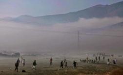 Afghani giocano a calcio, mentre altri camminano con il loro bestiame in una mattina nebbiosa a Kabul, Afghanistan