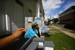 Photographer Carlos Barria holds a print of a photograph he took in 2005, as he matches it up at the same location 10 years on, in New Orleans, United States, August 17, 2015. The print shows Joshua Creek sitting on the porch of his house, September 13, 2005, after Hurricane Katrina struck. In 2005, Hurricane Katrina triggered floods that inundated New Orleans and killed more than 1,500 people as storm waters overwhelmed levees and broke through floodwalls. Congress authorised spending more than $14 billion to beef up the city's flood protection after Katrina and built a series of new barriers that include manmade islands and new wetlands. After photographing events a decade ago, Reuters photographer Carlos Barria returned to New Orleans. Using photos he took 10 years ago, Barria found the same locations that he documented originally and used the photos he took in 2005 to show the contrast of inundation then and a city now still affected by the disaster. REUTERS/Carlos Barria