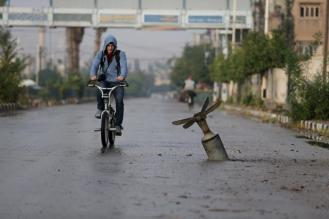 A resident rides his bicycle near what activists said was an exploded cluster bomb shell in the town of Douma, eastern Ghouta in Damascus November 5, 2015. REUTERS/Bassam Khabieh