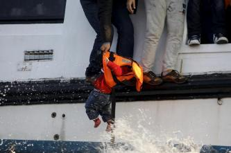 A refugee prepares to hand over a toddler to a volunteer lifeguard as a half-sunken catamaran carrying around 150 refugees, most of them Syrians, arrives after crossing part of the Aegean sea from Turkey on the Greek island of Lesbos, October 30, 2015. There were no casaulties amongst the refugees who were travelling on the catamaran, according to a Reuters witness. REUTERS/Giorgos Moutafis
