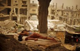 A Palestinian boy sleeps on a mattress inside the remains of his family's house, that witnesses said was destroyed by Israeli shelling during a 50-day war in 2014 summer, during a sandstorm in Gaza September 8, 2015. REUTERS/Suhaib Salem